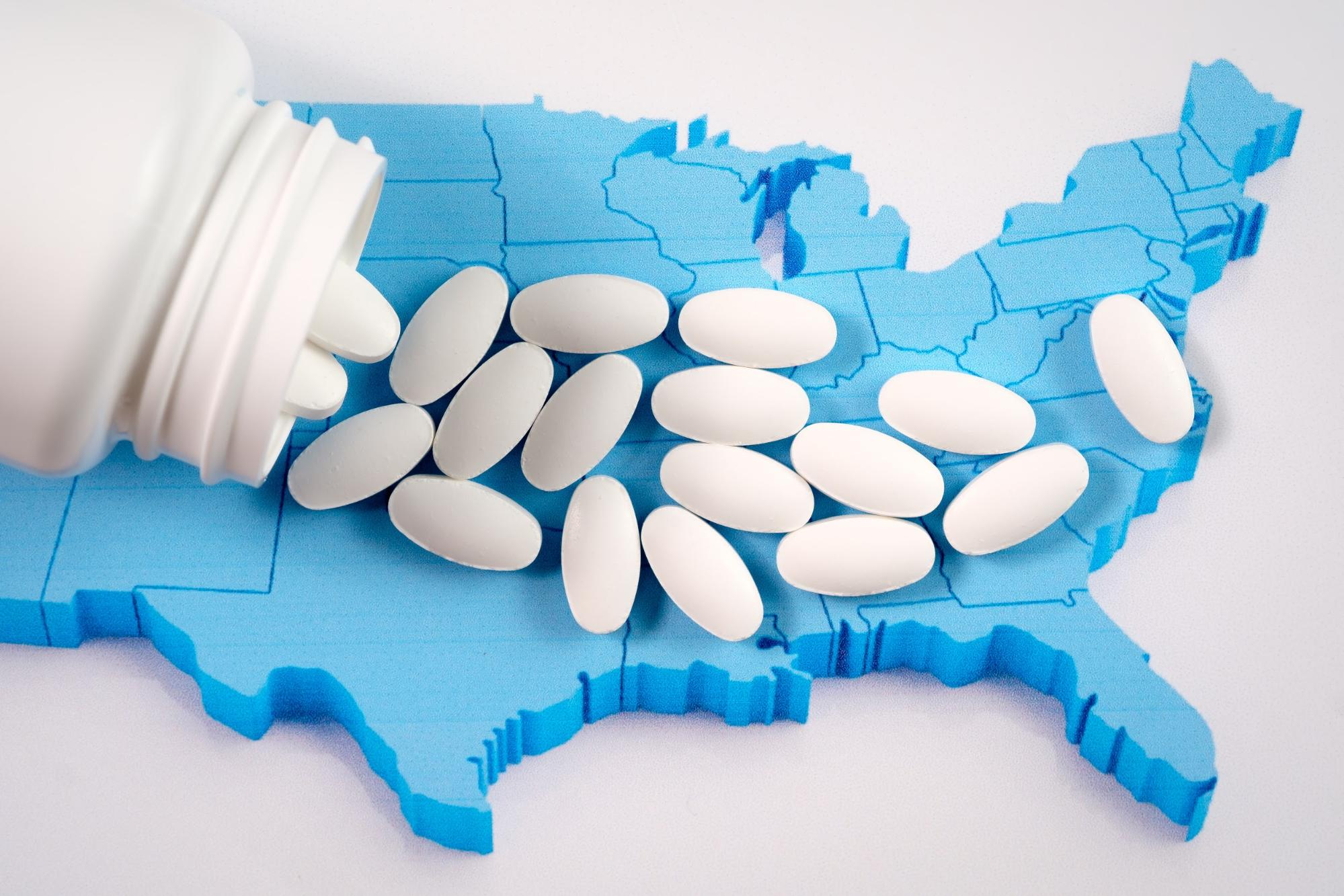 White pills spilled on top of a blue outline of the United States