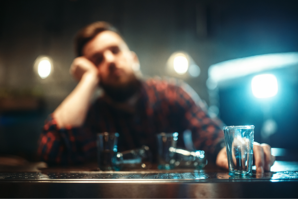 Close up of a shot glass with a blurry drunk man sitting at a bar in the background