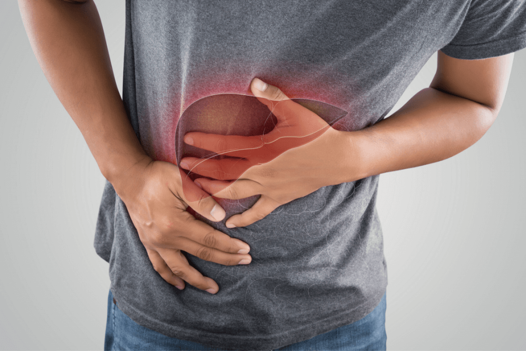 Close up of a man clutching his stomach due to liver problems