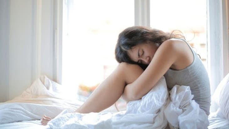 Woman sitting in bed unable to sleep
