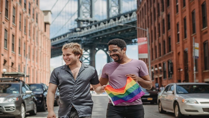 Happy gay couple strolling the street with the Pride flag