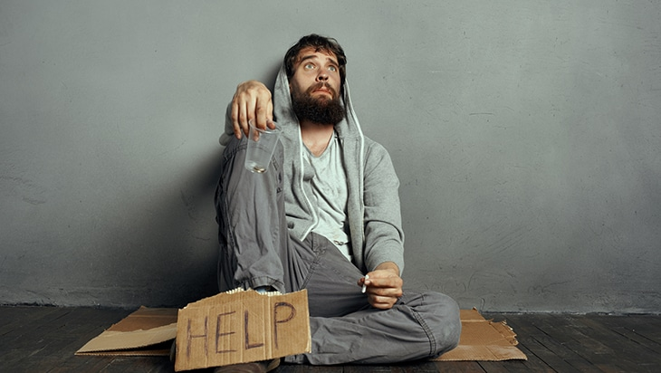 """A man sitting on the ground with a sign that says """"help"""""""