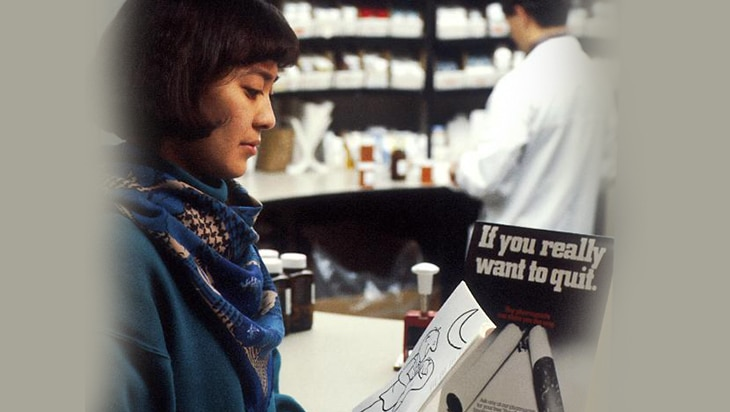 Woman in a pharmacy looks at a brochure for quitting smoking