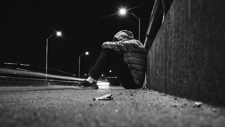 Man in hooded jacket sitting on the street at night.