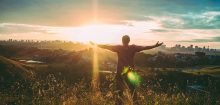 Happy man facing the sunshine with arms outstretched