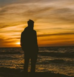 Silhouette of a person standing in front of the beach during sunset