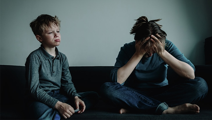 Mother and son crying on a couch