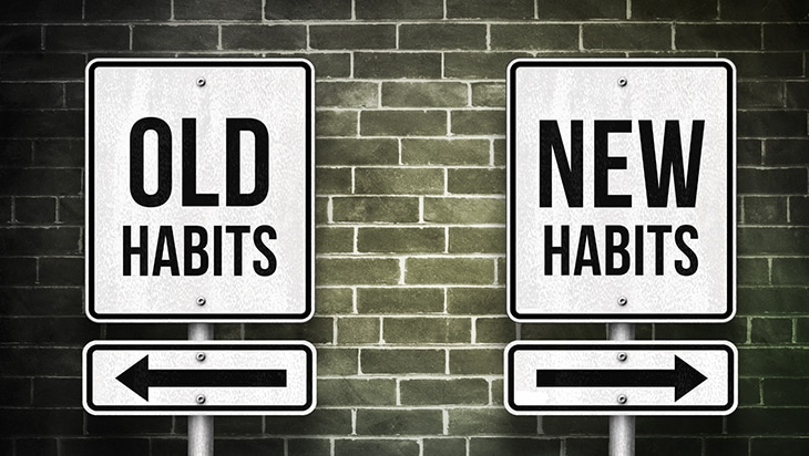 Two signs with arrows pointing left, towards old habits, and right, towards new habits