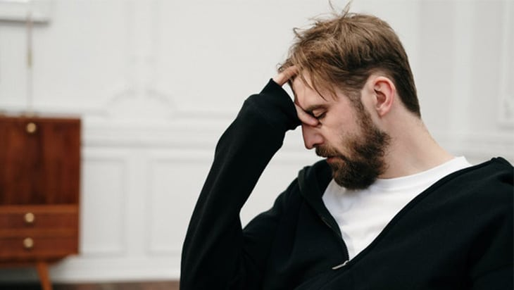 Man in a white shirt and black hoodie looking dishevelled and depressed