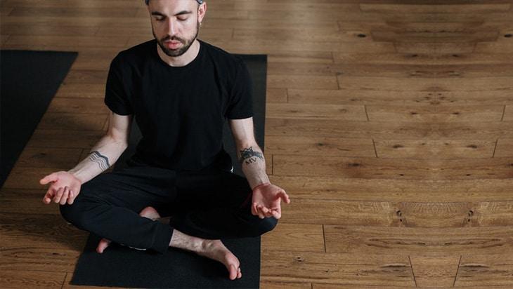 Man in black shirt and pants meditating
