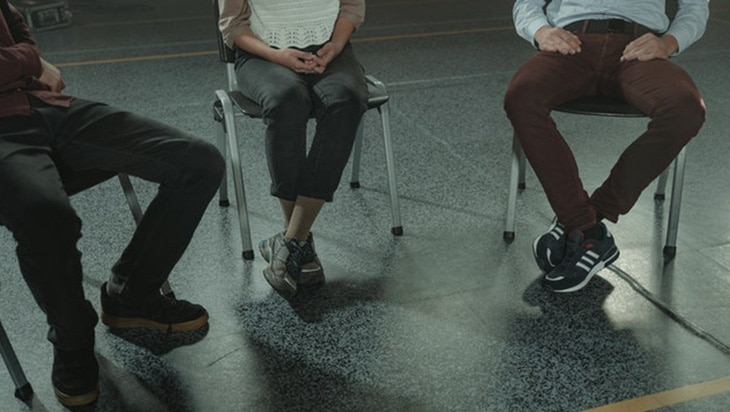 Three people sitting on chairs during a group counselling session