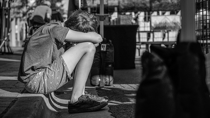Black and white photo of depressed teen sitting in a curb