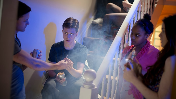 Teens at a party passing a joint around