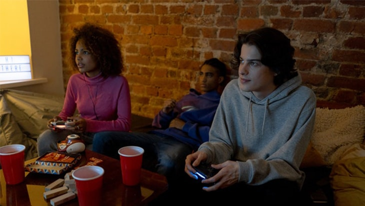 Teenagers playing video games while drinking