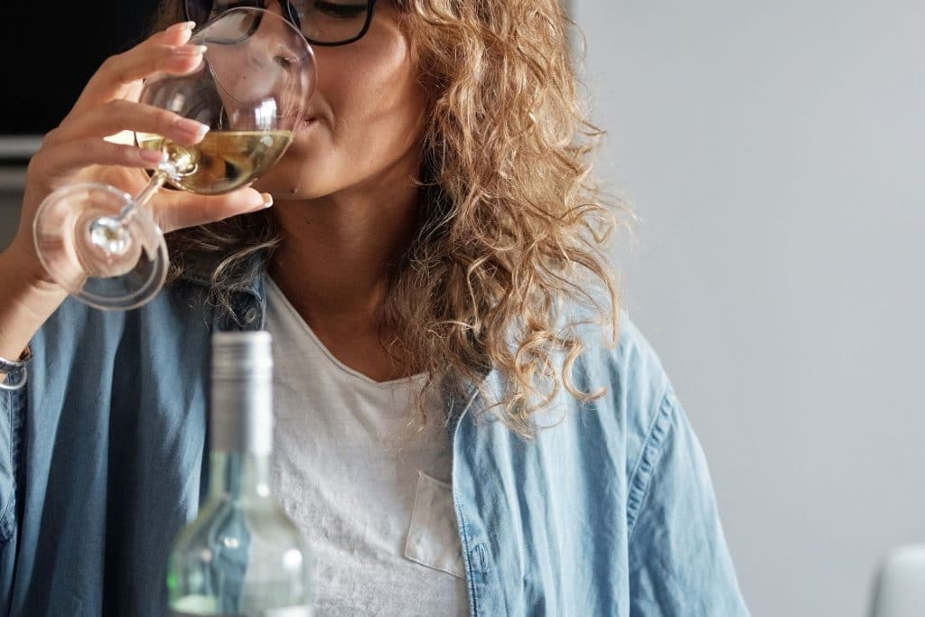 A woman sipping wine from a glass