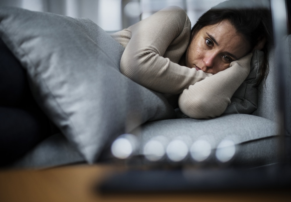 Depressed woman lying on the couch