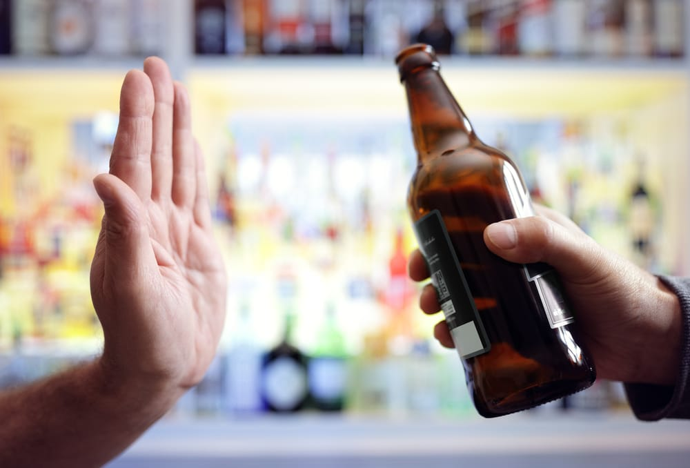 Hands refusing a beer