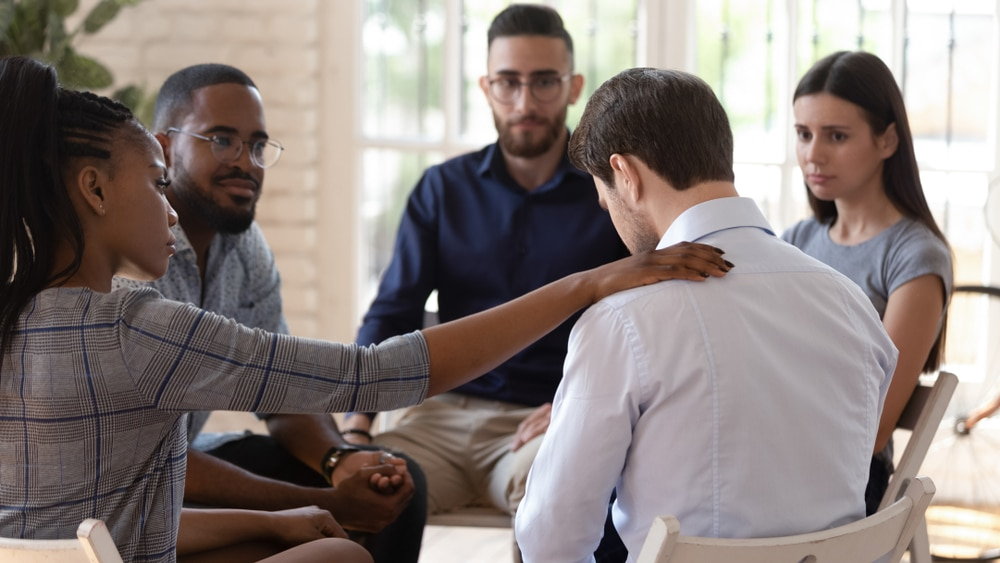 Man being comforted in a group counselling session