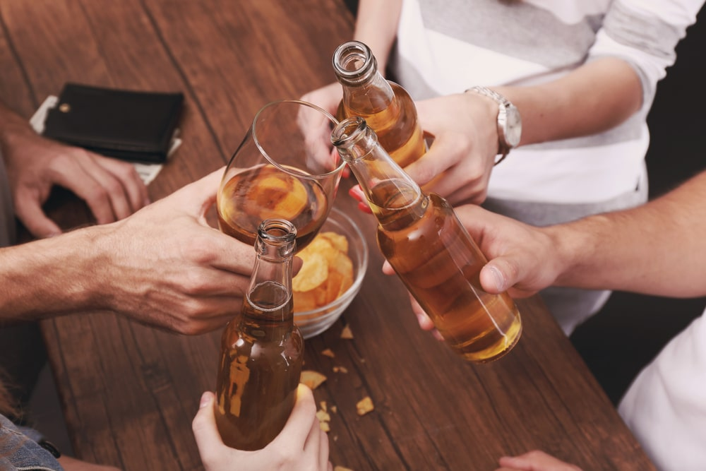 Several hands holding alcoholic drinks