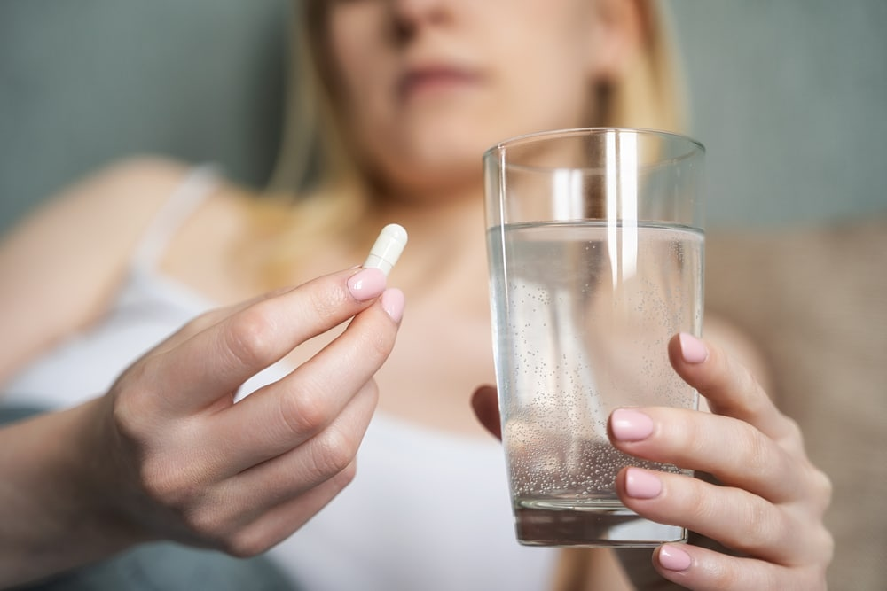 Woman holding a white capsule and a glass of water