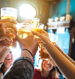 Group of people raising glasses with alcoholic drinks