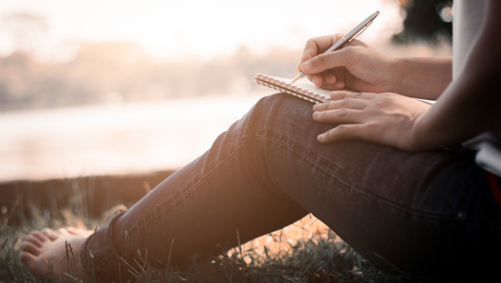 An individual writes down their addiction recovery goals with paper and pen