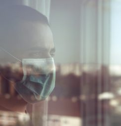 Man wearing mask looking out the window