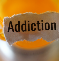 "a prescription bottle with a scrap piece of paper that reads ""addiction""."