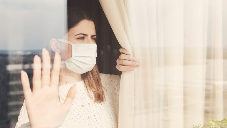 Woman wearing a mask in isolation seen from a glass window.