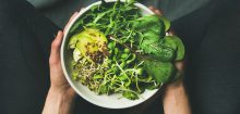 A bowl of leafy greens and sliced avocado
