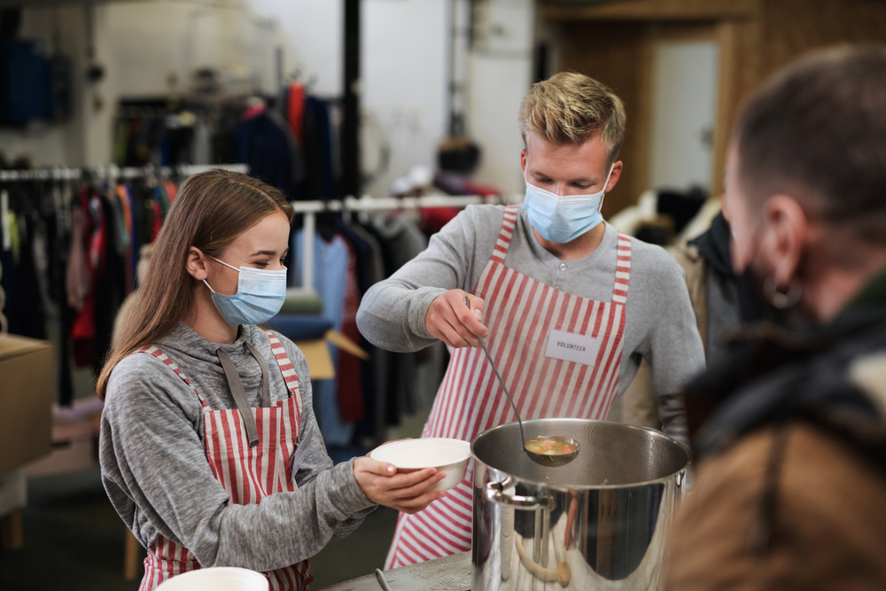 Volunteers serving hot soup for the homeless community.