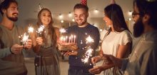 Friends celebrate recovery with cake and sparklers.